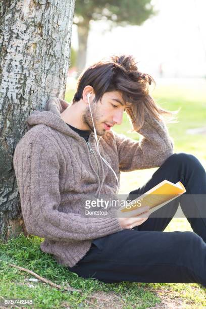 Young man reading book in the park.
