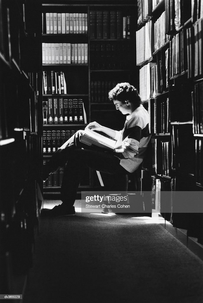 Young man reading in library : Stock Photo