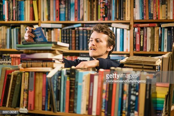 Young man reading in second hand bookstore