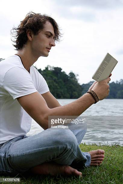 Young man reading, lakeside