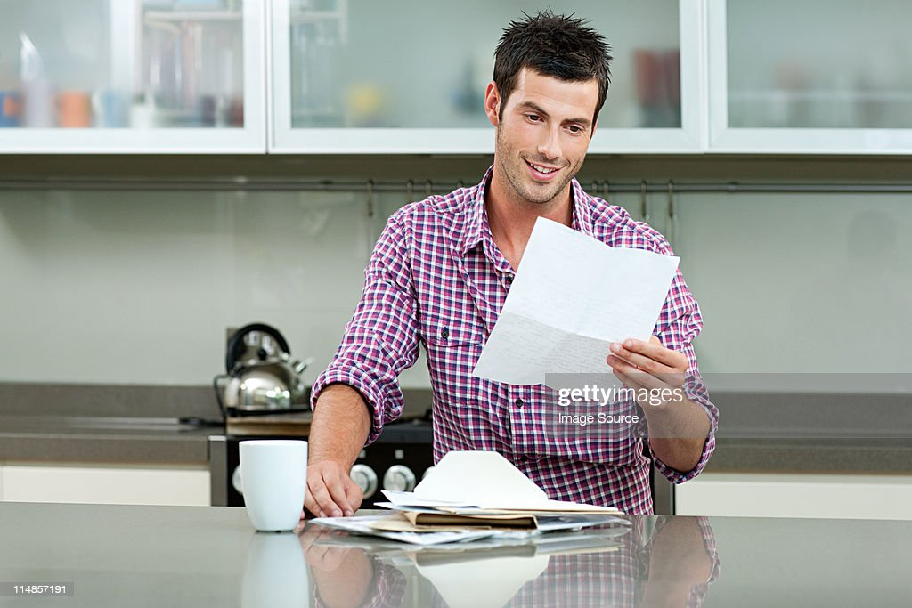 Young man reading letter : Stock Photo