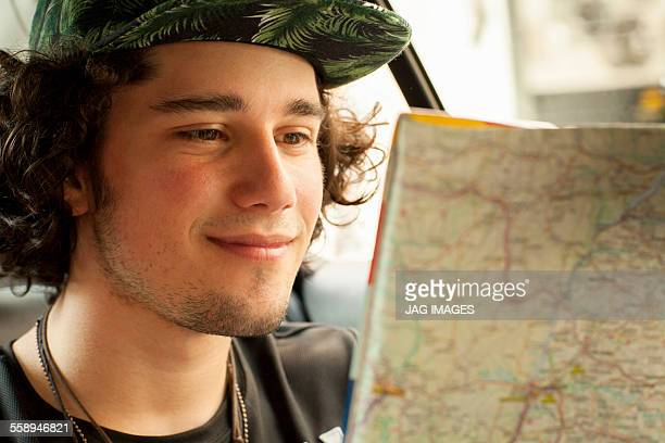 Young man reading map in back seat of taxicab, Rio De Janeiro, Brazil