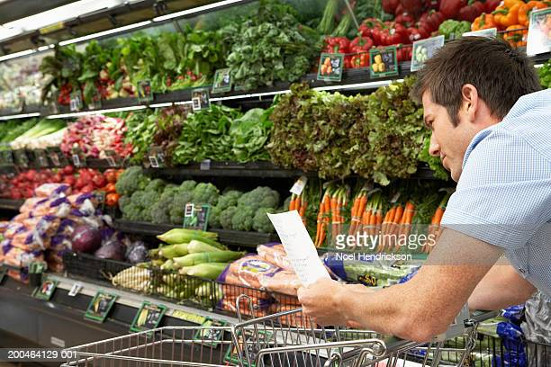 Young man reading shopping list in produce aisle, side view, close-up