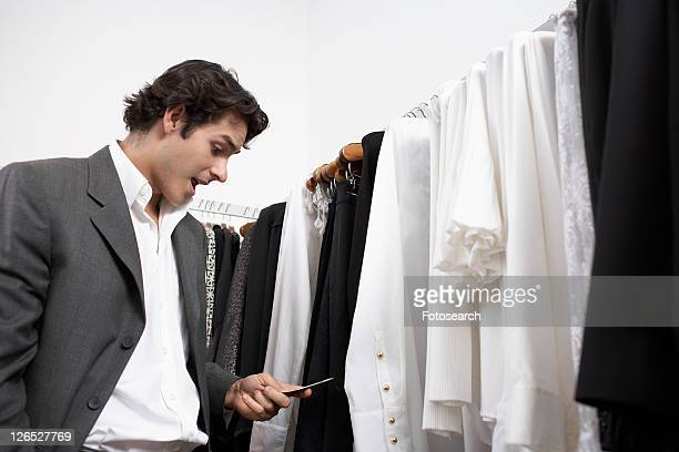 Young man reading text message in clothing store