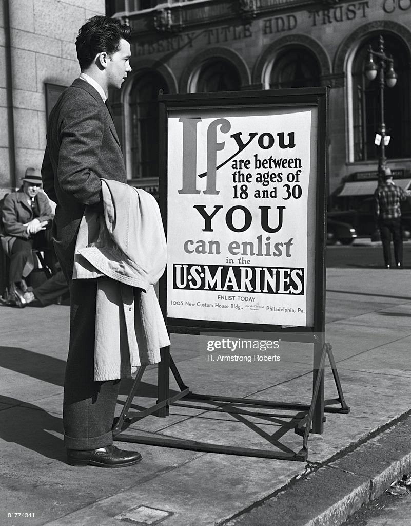 Young man reading US Marines recruitment post. (Photo by H. Armstrong Roberts/Retrofile/Getty Images) : Stock Photo
