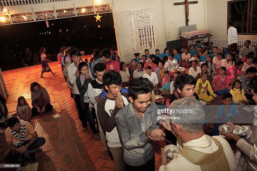 A young man receives the Sacred Host from the hands of Monsignor Enrique Figaredo during the Christmas Eve mass at the church of Tahen Village on December 24, 2013 in Battambang, Cambodia. The parish at Battambang dates back to 1790 when the Catholic community first arrived. Now they serve around 1000 Catholics and 600 families.