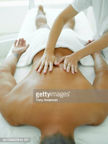 Young man receiving back massage in spa, elevated view : Stock Photo