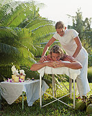 Young man receiving massage from young female masseuse, outdoors
