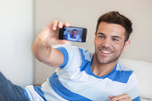 Young man reclining on bed taking selfie with smartphone