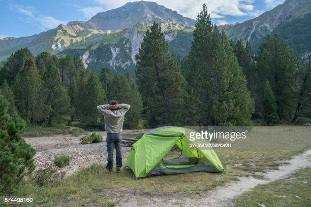 Young man relaxing beside tent at sunset, Switzerland