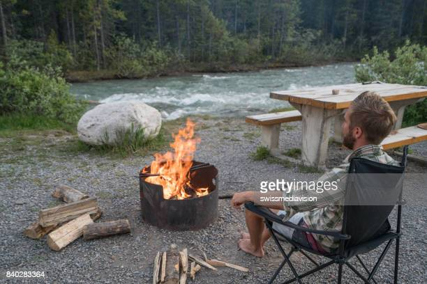 Young man relaxing by the fire at camp