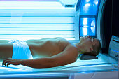 Handsome young man relaxing during a tanning in a modern solarium