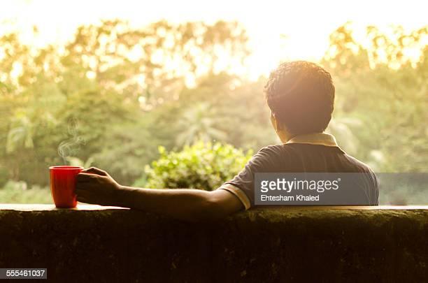 Young man relaxing in a garden having hot coffee