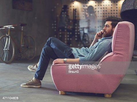 Joven relajante en el sofá y hablando en el teléfono.