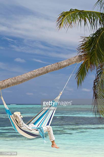 Young man relaxing in hammock hanged on a palm tree