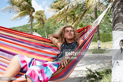 Young man relaxing in hammock on beach : Foto de stock