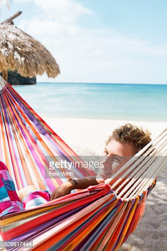 Young man relaxing in hammock on beach : Stock Photo