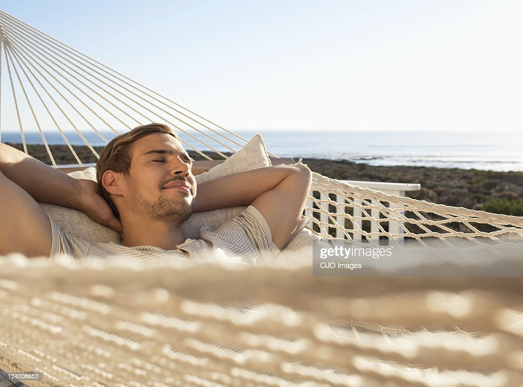 Young man relaxing in hammock with eyes closed : Stock Photo