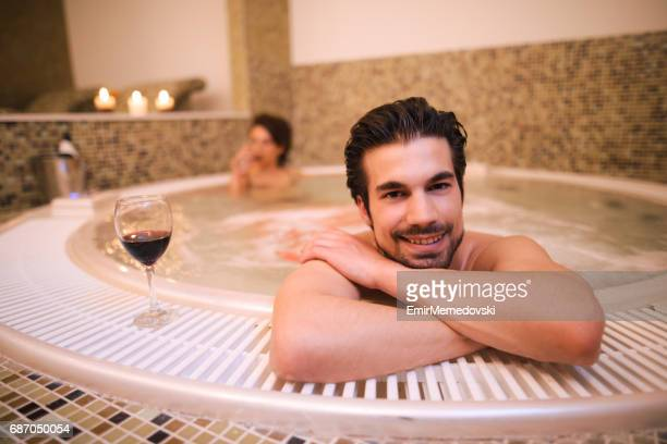 Young man relaxing in jacuzzi at health spa.