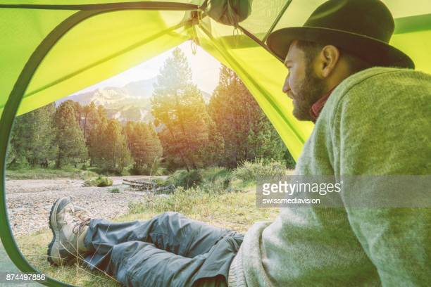 Young man relaxing in tent at sunset, Switzerland