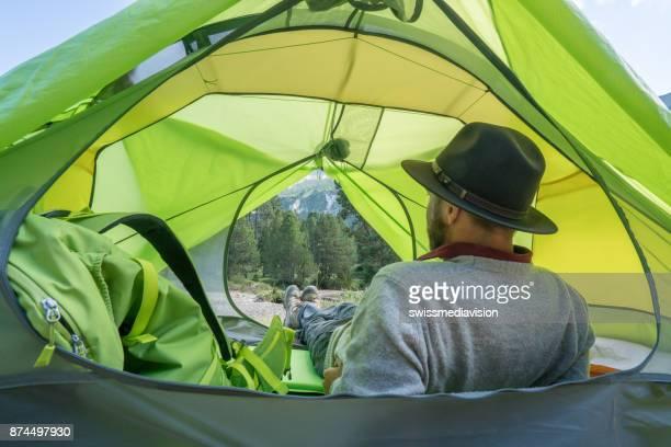 Jeune homme détente sous tente au coucher du soleil, Suisse