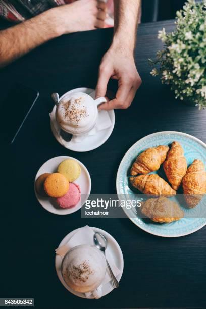 Jeune homme de se détendre dans le café, avec café et croissants