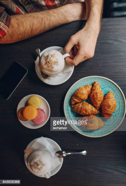 Young man relaxing in the cafe, with espresso and croissants