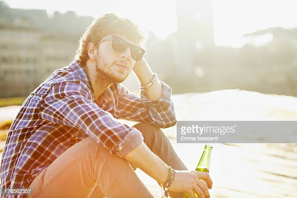Young man relaxing in the sun holding beer