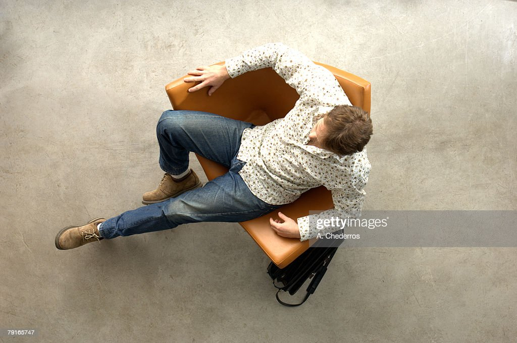 Young man relaxing on chair, overhead view : Stock Photo