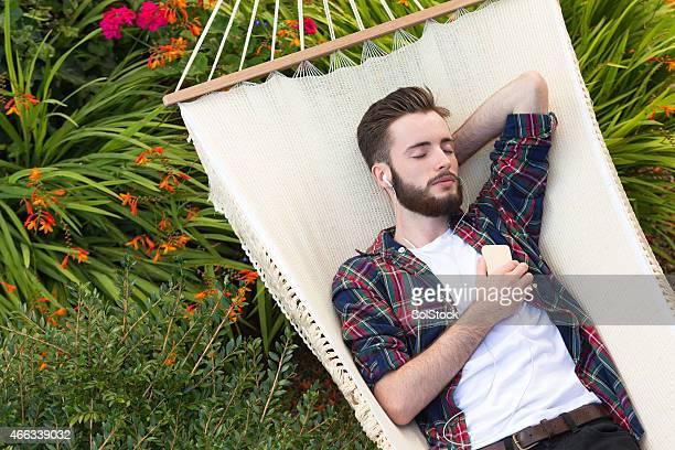Junger Mann Entspannen auf der Hängematte Musik hören