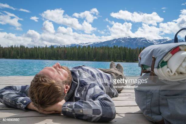 Young man relaxing on lake pier