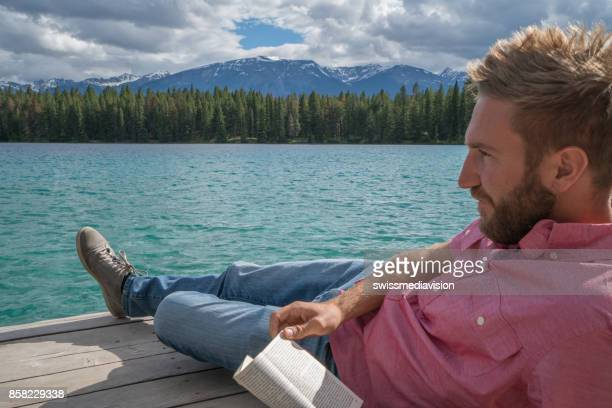 Young man relaxing on lake pier with book