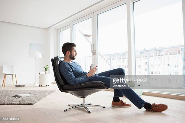 Young man relaxing on leather chair with cup of coffee in his living room