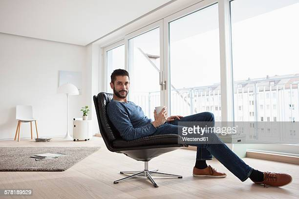 Young man relaxing on leather chair with cup of coffee