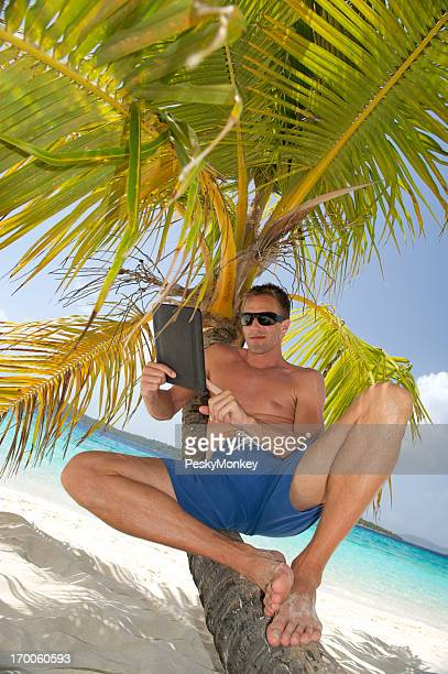 Young Man Relaxing on Palm Tree with Digital Tablet