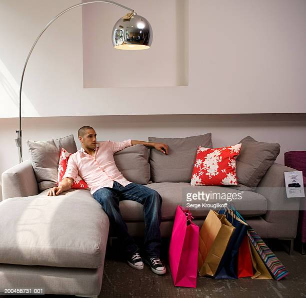 Young man relaxing on sofa in furniture shop, shopping bags by feet