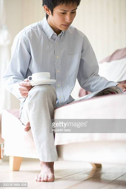 Young man relaxing on sofa, reading and drinking cup of coffee, low angle view