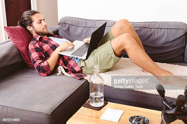 Young man relaxing on sofa, using laptop