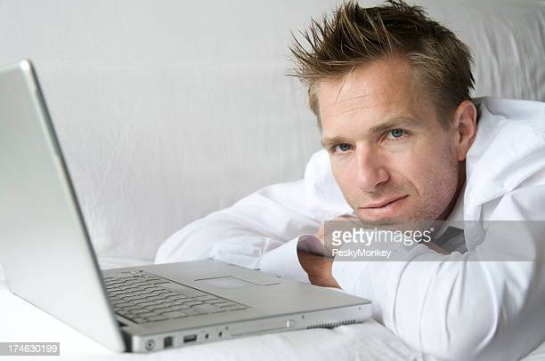 Young Man Relaxing on Sofa with Laptop Computer