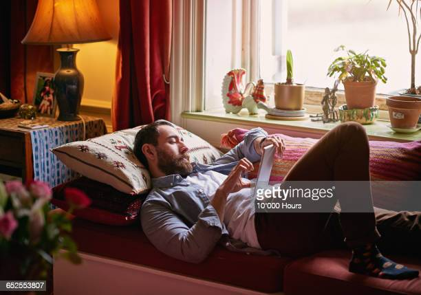 Young man relaxing using digital tablet