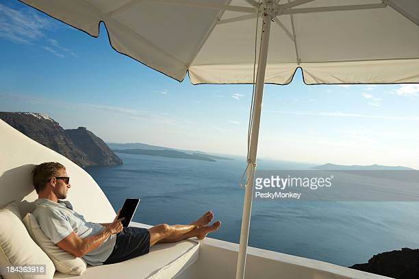 Junger Mann entspannend mit Tablet PC am Meer mit Balkon