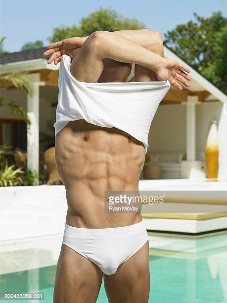 Young man removing shirt beside swimming pool, arms raised