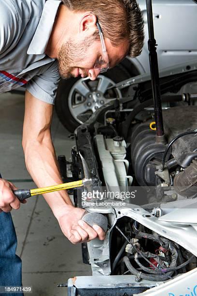 Jeune homme réparer la voiture dans un atelier de carrosserie