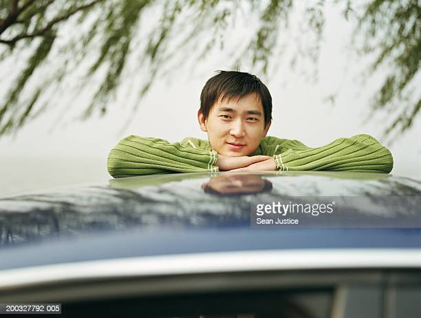 Young man resting arms on roof of car, portrait