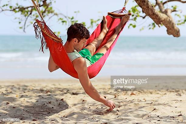 Young man resting in hammock on beach