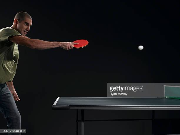 Young man returning ball in table tennis match, side view