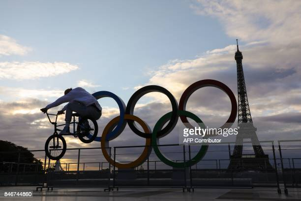 A young man rides an acrobatic bike at sunrise by the Olympic rings installed on the Esplanade du Trocadero near the Eiffel tower following the...