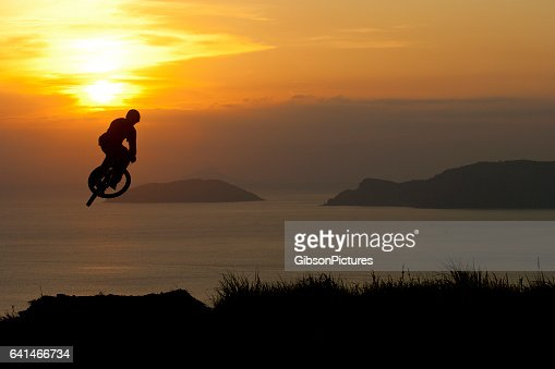 A young man rides off a big jump as the sun sets on the ocean.