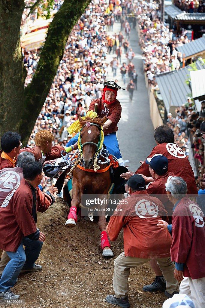 A young man riding a horse runs up the hill during the 'Uma-Age' ritual at Tado Taisha Shrine on May 4, 2014 in Kuwana, Mie, Japan.