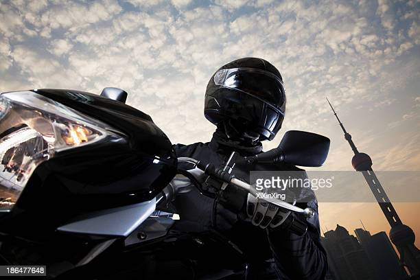 Young man riding a motorcycle during the day, sky and building exteriors in the background